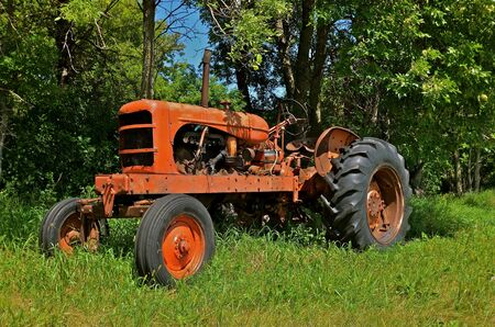 machinery: Antique orange tractor parked along the wood line