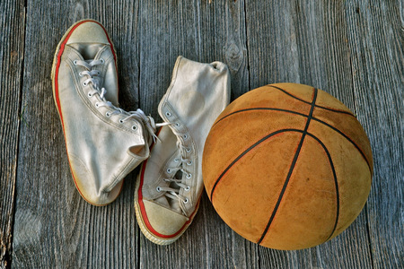 Leather basketball and a pair of vintage gym shoes photo