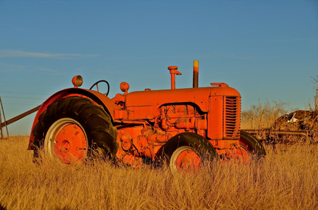 int: Old orange tractor parked int he field Stock Photo