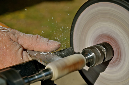 Woodworker turning a spindles on the wood lathe