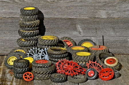 lugs: Piles of toy tractor tires and rims are stacked on a weathered wood  background