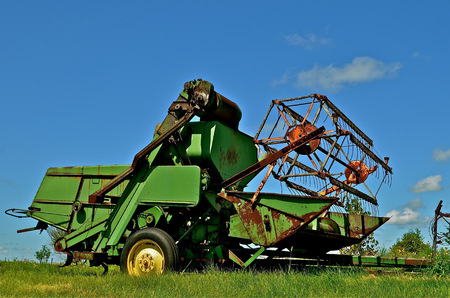 Old green combine parked in the field