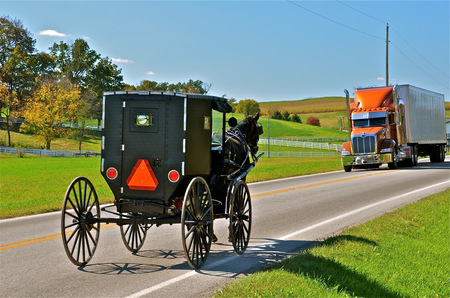 Amish buggy and huge semi share the roadway