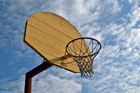 Old wood basketball backboard, rim, and net against the sky Banco de Imagens