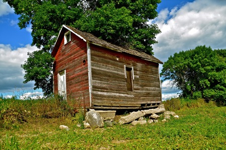 crumbling: A red weathered old granary sits atop of a crumbling foundation along side of a pasture