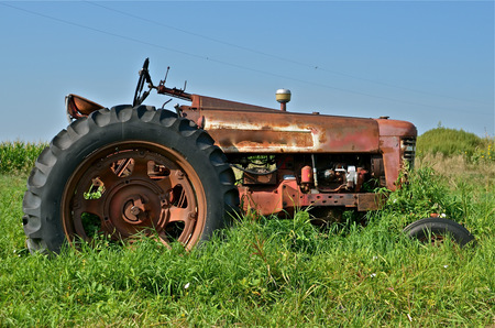 An old vintage rusty red tractor is parked in the long grass Banco de Imagens