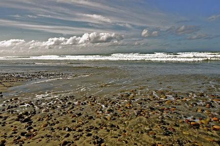 carlsbad: Ocean beach full of round rocks as tide rolls in