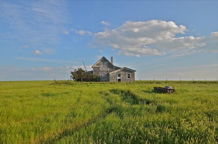 Old weathered farm house sits isolated on the vast prairie photo