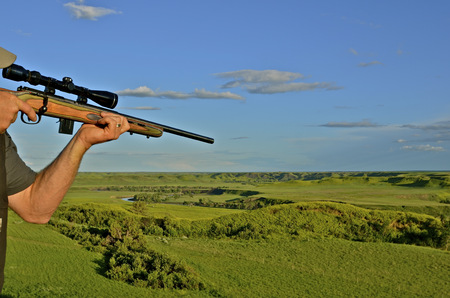 Hunter with rifle and scope takes aim Banco de Imagens