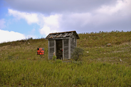 latrine: A weathered old outhouse situated on a hillside serves as a rest stop for travelers