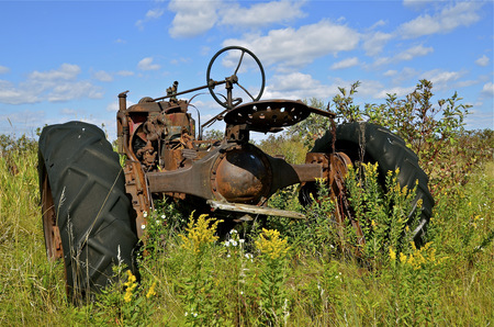 Rusty dilapidated tractor parked in the weeds and grass photo