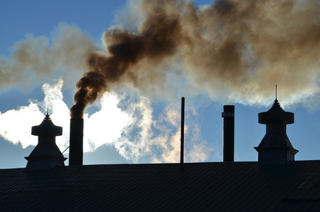 cupolas: Old industrial plant with cupolas billows black coal filled smoke from its chimney