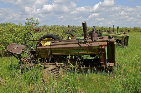 Several od tractors are lined up in the brush and grass photo