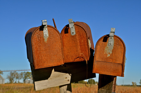 usps: Three old rusty mailboxes in a rural country town