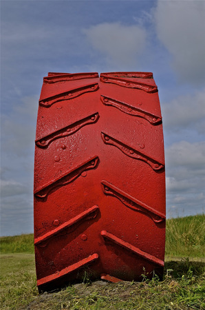 lugs: Large painted, steel wheel of a very old tractor