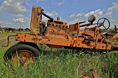 An old tractor with a crank for starting has been stripped of many parts in a junkyard and salvage company.