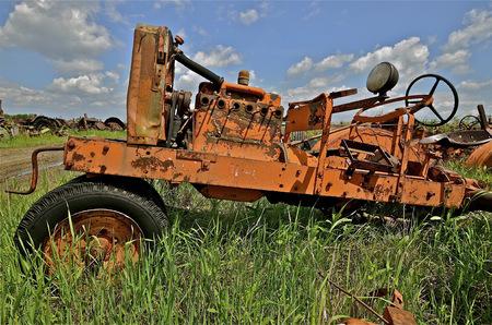 Um trator velho com uma manivela para partida foi despojado de muitas peças em ferro-velho e uma empresa de salvamento.