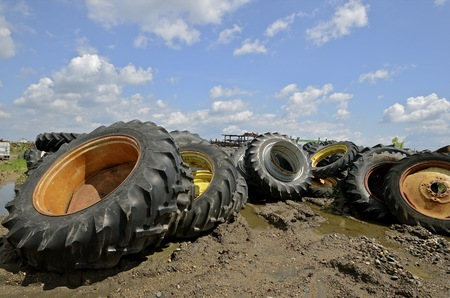 Huge tires and rims tractors and heavy equipment are stacked in a salvage junkyard Stock Photo