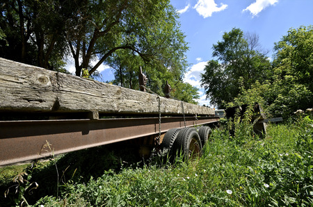 A semi trailer with heavy beams for loaded is parked in the long summer grass photo