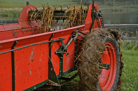has been: A refurbished red manure spreader has been very recently used Stock Photo