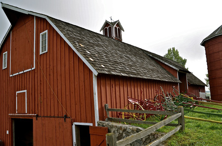 refurbished: Old horse drawn machinery is stored along the side of a refurbished hip roofed barn