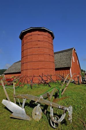 old red barn: An old refurbished plow sits in front of a red barn and wooden  stave silo
