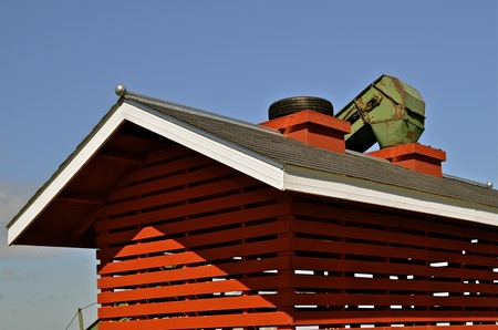 drying corn cobs: A red  corn crib with slats for drying is ready to receive corn from the elevator which is in place Stock Photo
