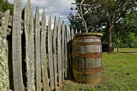 cooper: An old wood barrel is left along a weathered fence line Stock Photo