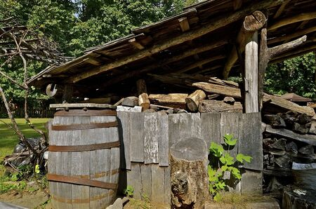 overhang: The weathered overhang of of old shed provides a dry storage area for chopped firewood,