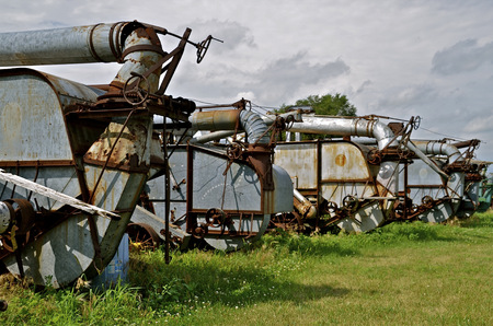 thresh: A series of old threshing machines are lined up for display exposing the blowers