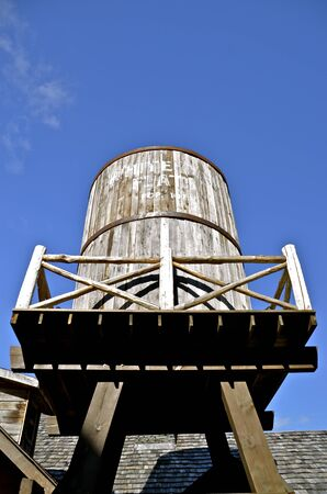 A large wooden water barrel is perched upon supporting posts and beams