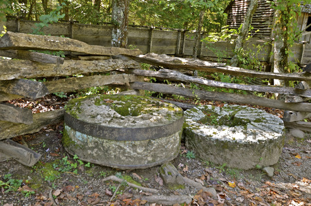 Several millstones along an old weathered wood fence