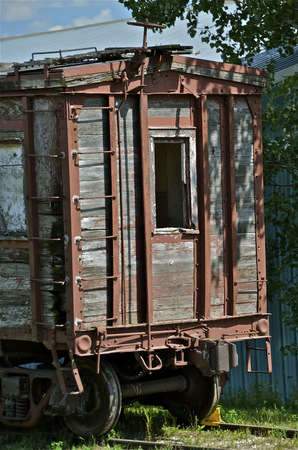 caboose: An old railroad car with wood siding  rests on a railroad track. Stock Photo