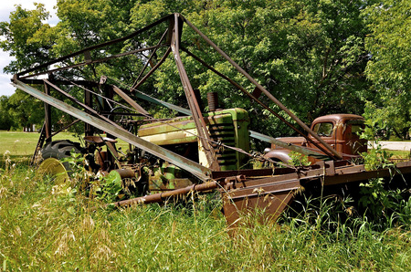 An old end with a large front end loader is left to deteriorate in the woods with an old pickup Stock Photo