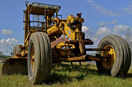grader: An old vintage road grader used on gravel roaders is ready for usage.