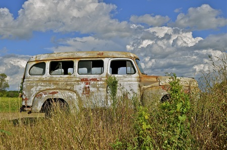 rusty car: Old rusty van  parked in the weeds