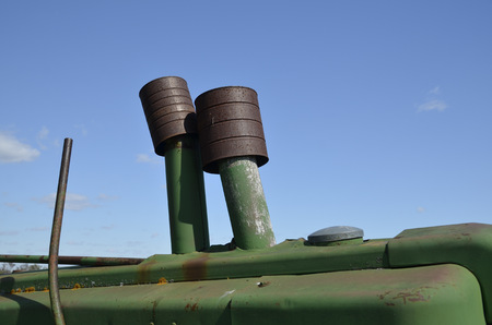 old tractor: Tin cans cover the exhaust openings on an old tractor