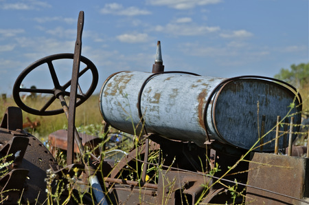 junkyard: The gas tank of a very old tractors sets on the frame of the junkyard tractor Stock Photo