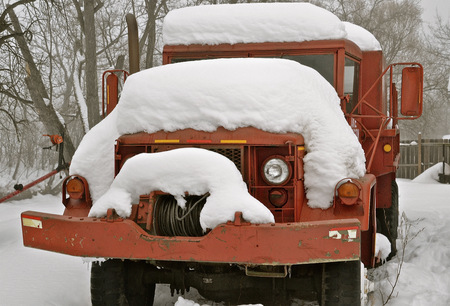 wench: Old antique large emergency vehicle with a front cable for towing and welching stalled  cars is covered with snow.