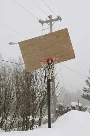halted: A crooked backboard  and snow covered outdoor basketball court has halted any activity