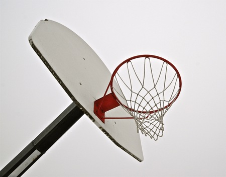 Basketball hoop, net, and board silhouetted against foggy sky