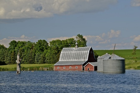Rising lake levels floods farm building and grain tanks photo