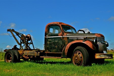 wench: An old rusty tow truck with a wench in the back is parked in the grass. Stock Photo