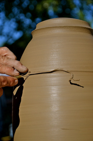 A potter is scribing a lamp base as it turns on the wheel