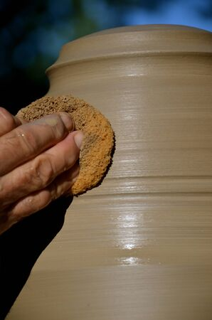 damping: An artist is using a sponge to damping the clay on a lamp base as it turns on the potter;s wheel