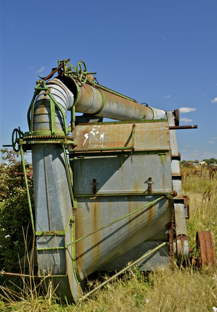 thresh: old threshing machine parked in a junkyard with the blower pipe  resting on top frame Stock Photo