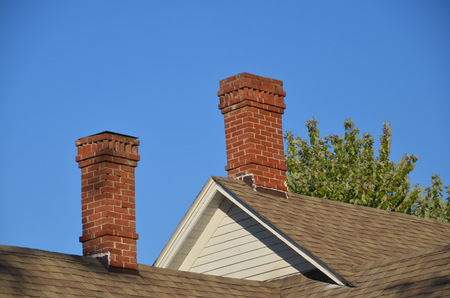 Several brick chimneys on an old house have need for a chimney sweep Archivio Fotografico