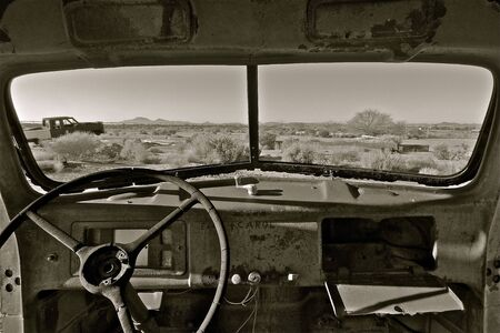 junk: Old vehicle with crank out windows left in a junkyard in a desert