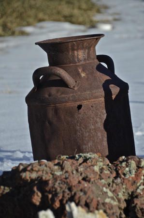 milkman: Rusty milk can sitting on a rock in the snow
