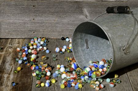roll out: Marbles roll out of a galvanized shotgun can